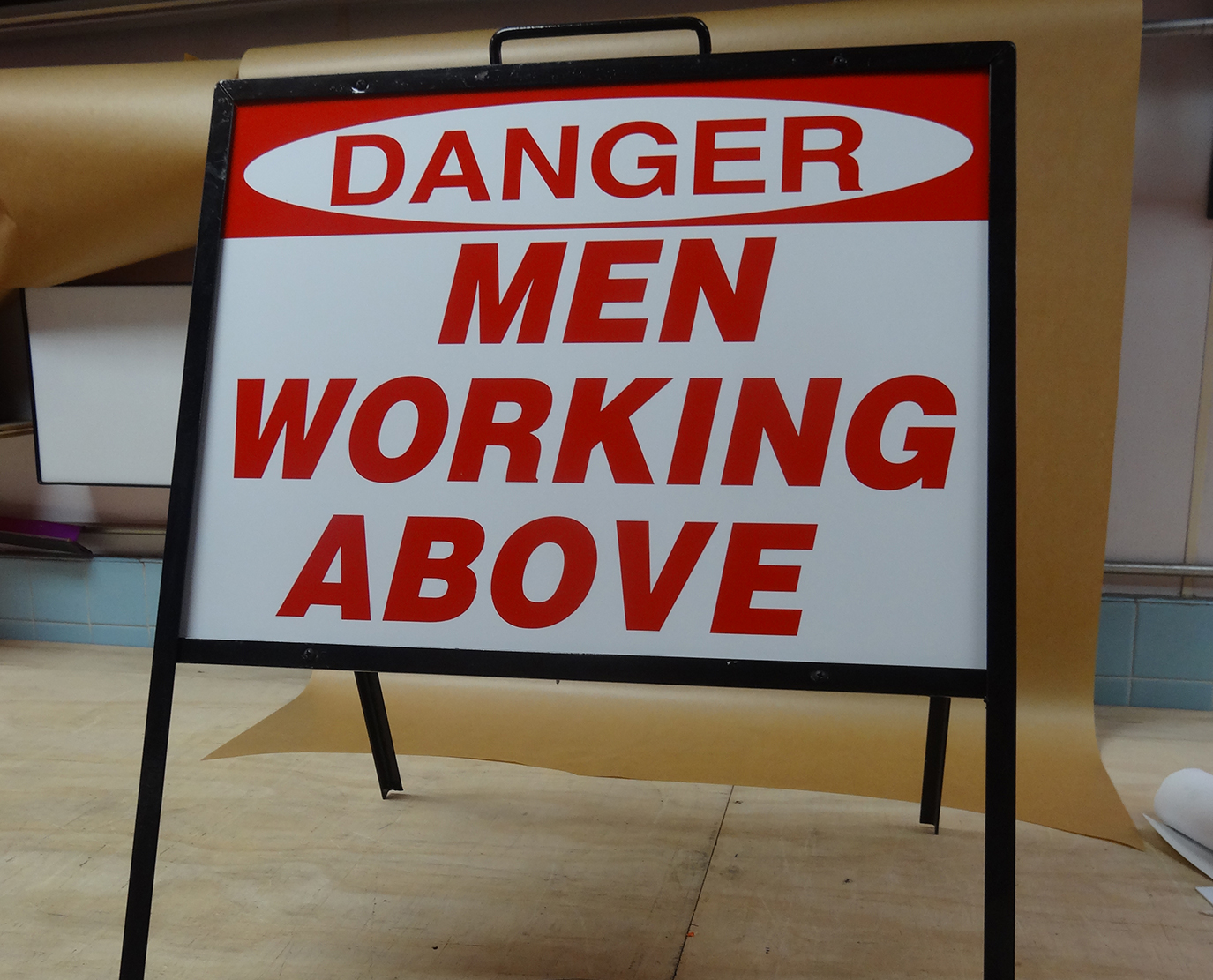 Man Working Above Job site sign